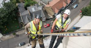 2 Axis workmen carrying out external wall insulation whilst abseiling.