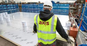 Axis worker laying new insulation titles on the roof of the building
