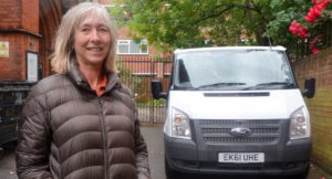 Fundraising Manager of the Upper Room stood in front of a van donation to the charity by Axis