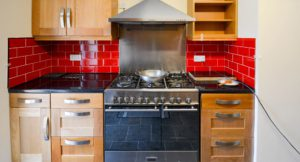 New kitchen with double oven and red tiles.