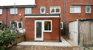 Home extension in red brick with patio door leading to paved garden.