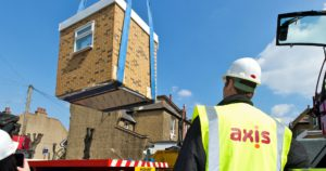 Pre built bathroom being hoisted off a wagon by a crane whilst Axis worker oversees.