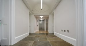 Newly renovated metal lift with original stone flooring and white walls.