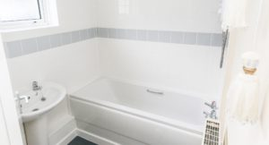 Newly installed white bath surrounded by white and grey tiling