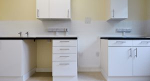 White kitchen cabinets with grey work surfaces and floor tiling.