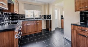 Black floor and wall tiling with dark chestnut laminated cupboards and black work surfaces.