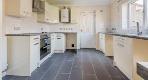 White kitchen cupboards with grey work surfaces and flooring tiles.