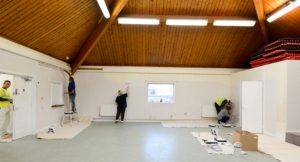 Axis workers painting the interior of the community centre in magnolia paint.