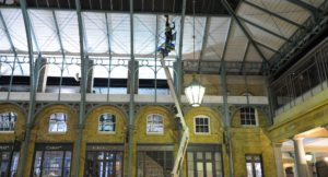 Workman in cherry picker cleaning the cast iron arches.