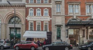 Red brick with off -white stucco and a pale blue awning covering the front of the shop with Penhaligons scribed onto it.