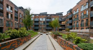 5 story flat buildings surrounding a courtyard with greenery.