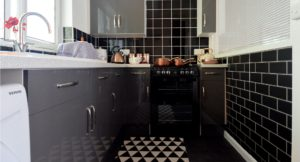 Grey gloss cupboards with black wall and floor tiling.