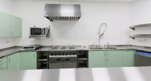 Fully equipped stainless steel commercialkitchen with mint green cabinets.