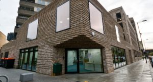 Brick two storey community hub with large windows, extended onto residential block of flats