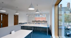 Second floor work space with large windows and white pendant lighting.
