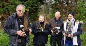 Four volunteers from Axis holding young trees ready to plant.