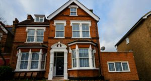 3 storey red brick Victorian house with a pitched roof and loft conversion