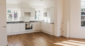 Large kitchen area with walnut wooden flooring, white cupboards and built in appliances