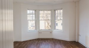 Interior living room bay window with white walls and walnut flooring