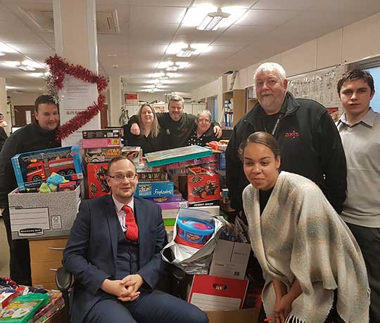 A group of Axis employees surrounded by donated toys in Kingston office