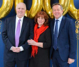 two men in suits flanking lady in red scarf with golden balloons in background