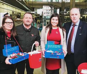 A team of Axis volunteers with fundraising buckets and poppies at Canary Wharf station