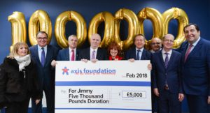 group photo showing large cheque for five thousand pounds and golden balloons