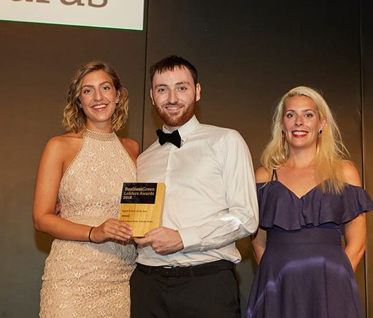 Two women and one man in formal dress accepting Business Green Award