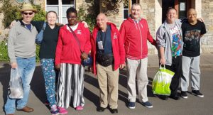 Group adults some wearing red jackets in front of Booking Office
