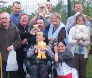 Group of vulnerable people, holding bears, one in fore in a wheelchair