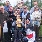 Group of people holding teddies, one in wheelchair, one holding plastic bag