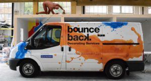 White van with blue and yellow splashes of paint, says bounce back on side