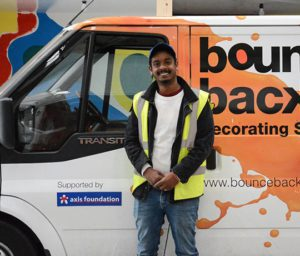 Young man in high vis jacket in front of van with yellow paint splsshes, bounce back and axis foundation logos