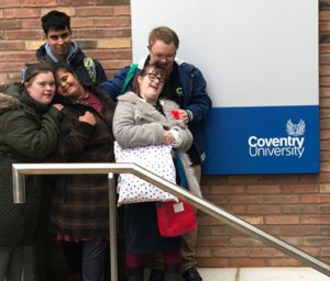 Smiling young people standing on stairway outside Coventry University