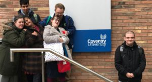 group of young people standing on steps by Coventry University sign