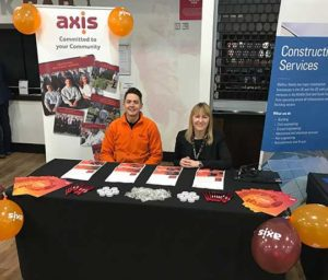 Two employees sat behind an Axis stall at National Apprenticeship Week event.