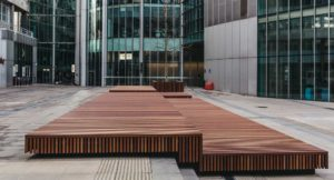 Low level wooden bench street furniture covering steps.