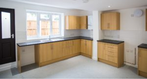 Interior shot of kitchen, gray floors, brown wooden units and dark marble effect worktop with sink below window