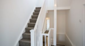 Interior shot of upper landing and white painted wooden stair rail, gray carpet and white walls