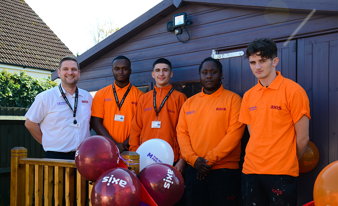 Axis apprentices stand in front of a new sensory barn installed for children at the maypole project