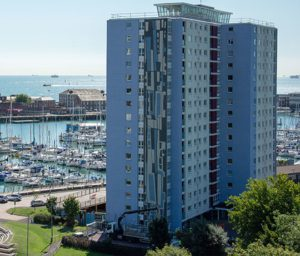 Gosport Tower exterior shot with tile detail to side of building, harbour in background