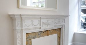 Interior shot of ornate carvings round white fireplace with painted mirror