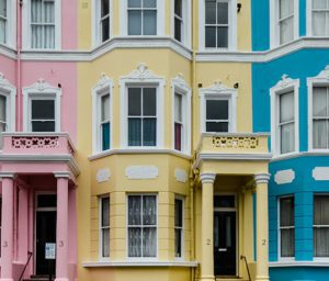 Exterior shot of 3 pink, yellow and blue buildings with pillared entrances