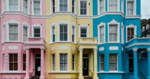 Exterior shot pillared entrances 3-storey pink blue and yellow houses