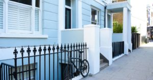 Pale blue building with bike attached to black railings