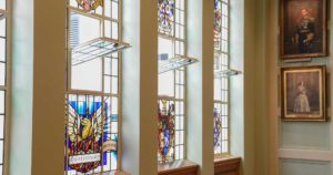 Stained glass windows with crests, portraits on wall