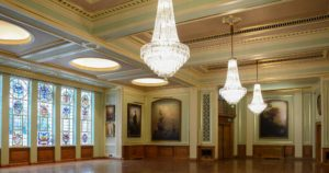 Chandeliers in banqueting hall with wooden floor and pastel walls