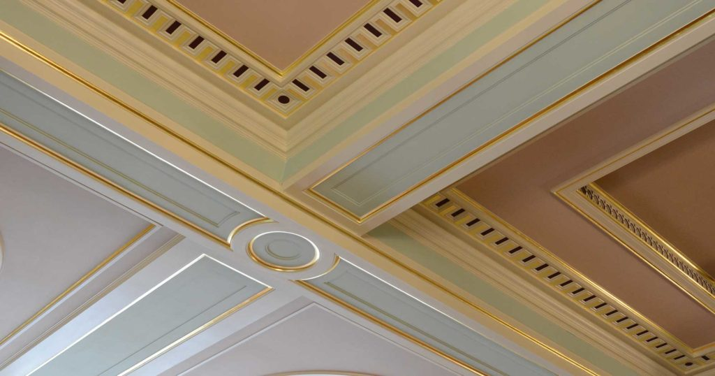 Close up of gold leaf and pastel colours on centre of painted ceiling