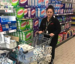 lady shopper in supermarket with full trolley kitchen rolls