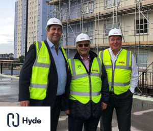 Three Axis people in high vis and hard hats on site with Hyde logo in corner
